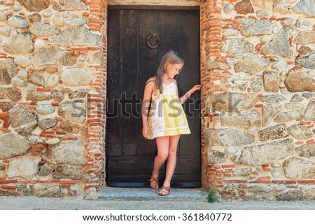 Outdoor fashion portrait of a cute little girl wearing yellow dress - stock photo