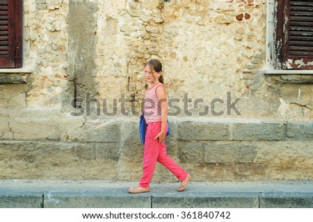 Outdoor fashion portrait of a pretty little girl, wearing red summer clothes, holding blue bag - stock photo