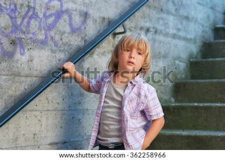 Outdoor fashion portrait of adorable little boy wearing purple shirt - stock photo
