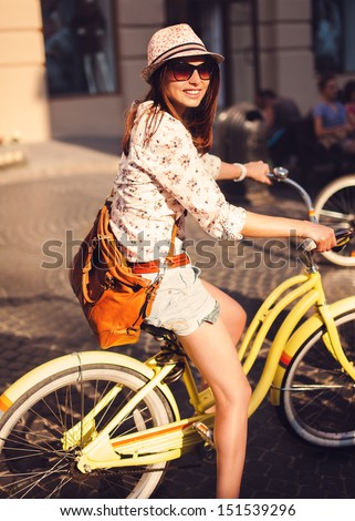 Outdoor fashion portrait of attractive young brunette in a hat on a bicycle. - stock photo