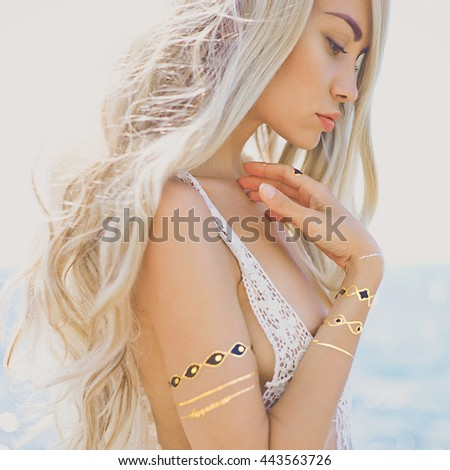 Outdoor fashion portrait of beautiful blonde lady at beach with flash tattoo - stock photo