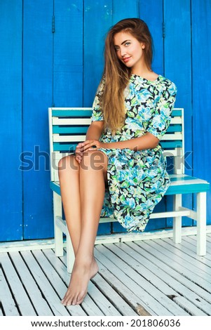 Outdoor fashion portrait of beautiful female model posing outdoor at blue background, wearing stylish midi retro floral dress, have blonde straight hail and perfect tan legs. - stock photo