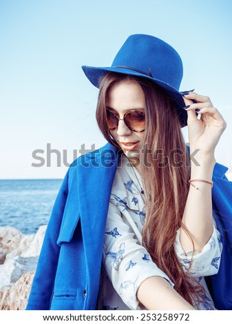 Outdoor fashion portrait of beautiful model, wearing warm stylish outfit with coat and sneakers in city yacht club. Autumn street style. - stock photo