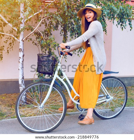 Outdoor fashion portrait of crazy smiling laughing young brunette girl having fun with her retro hipster bicycle, wearing stylish vintage clothes and straw hat, having fun alone at fall autumn day. - stock photo
