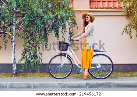 Outdoor fashion portrait of elegant lady riding her hipster retro bike in vintage stylish maxi skirt warm cardigan and straw hat. enjoy mica fall autumn day, posing at the street with birch trees. - stock photo