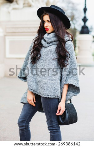Outdoor fashion portrait of glamour sensual young stylish woman wearing trendy fall outfit , black  hat , grey sweater and leather bag. Bright red  lips. Old city background. - stock photo