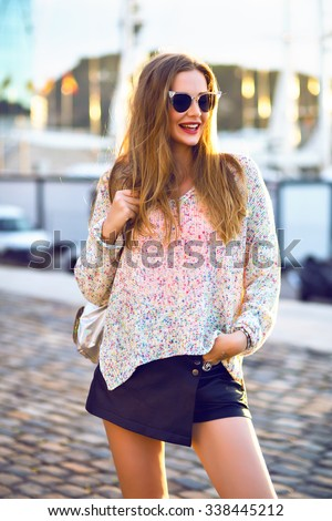 Outdoor fashion portrait of pretty blonde woman walking alone at nice sunny autumn day, cozy swather mini skirt, evening sunlight. - stock photo
