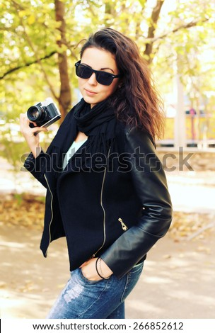Outdoor fashion portrait of stylish photographer girl holding vintage retro camera, wearing trendy sunglasses and leather jacket. Lifestyle portrait bright toned colors. - stock photo