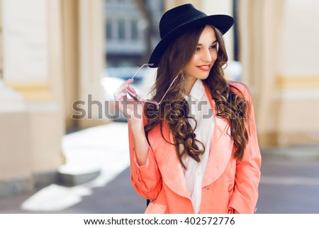 Outdoor  fashion portrait of stylish  pretty brunette  woman in night spring casual outfit walking in the city. Wearing white blouse, pink jacket, black wool hat. Long wavy hairstyle. - stock photo