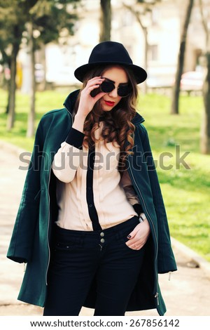 Outdoor fashion portrait of stylish pretty hipster girl wearing green coat, sunglasses and vintage hat, walking on the street in nice sunny day. Sensual young lady. Lifestyle, toned instagram filters - stock photo