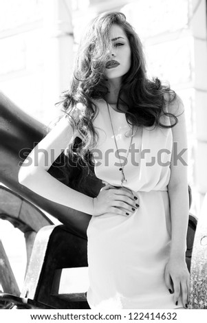 outdoor fashion portrait of young beautiful fashion woman with long brown hair and red lips - stock photo