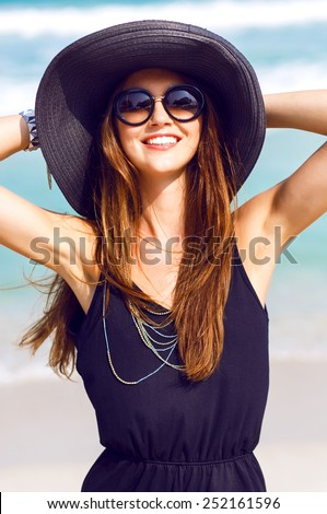 Outdoor fashion portrait of young happy pretty smiling woman, having fun on the beach, wearing stylish boho chick outfit hat and sunglasses, positive mood. - stock photo