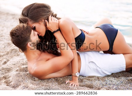 Outdoor fashion portrait of young sexy sensual couple lay on the beach.passion between two lovers.Love on the beach,tender kisses and touching passionate between two peoples.man and his girlfriend - stock photo