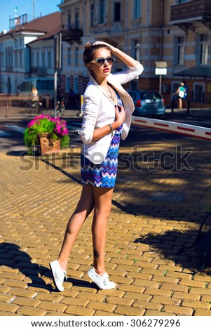 Outdoor fashion portrait of young stylish hipster elegant girl, walking alone at sunny day, at European city center, wearing romper, jacket and sunglasses, joy, vacation, travel, bright colors.