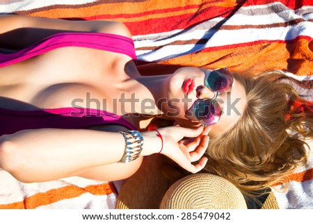 Outdoor fashion portrait summer beach style of young beautiful blonde woman fresh face smiling on the beach of tropic island having fun on vacation in trendy bikini and sunglasses,sunbathing,kisses  - stock photo
