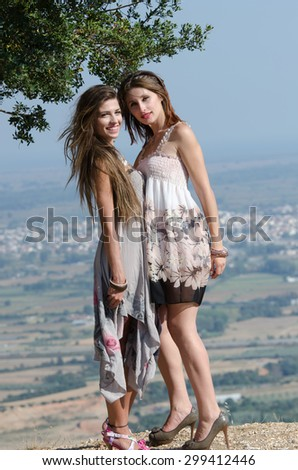 Outdoor fashion shot of two young women in dress