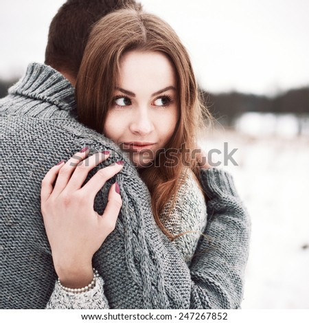 Outdoor fashion stylish sensual portrait of beautiful couple in love posing in winter cold snow field  - stock photo