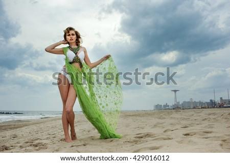 Outdoor fashion summer photo of beautiful slim woman with perfect body in luxury design bikini on the beach. - stock photo