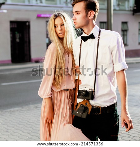 Outdoor fashion summer portrait of young pretty stylish hipster couple of brunette man and blonde woman posing on the street