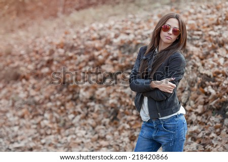 Outdoor fashion toned colors portrait of young sexy woman in jeans, jacket and sunglasses. Model posing. Copy space - stock photo