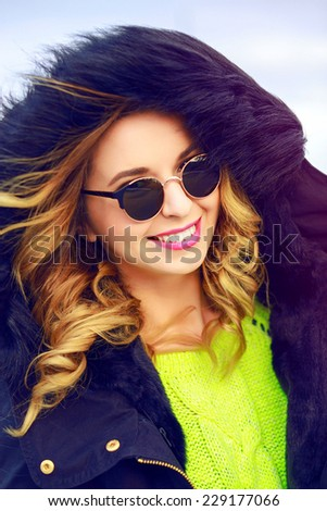 Outdoor fashion winter portrait of pretty stylish woman wearing neon sweater, stylish warm parka and sunglasses, have amazing smile and curled hairs. - stock photo