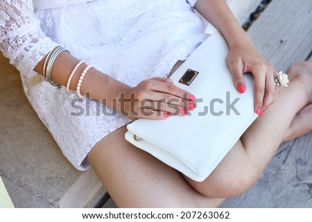 Outdoor fashion young woman hold white clutch with pink manicure - stock photo