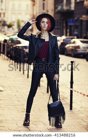 Outdoor full body portrait of young beautiful fashionable lady posing on the street. Model wearing wide-brimmed hat and stylish leather clothes. Girl looking at camera. Female fashion. City lifestyle