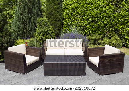 Outdoor furniture in green garden with with chairs, sofa and table in a patio. - stock photo