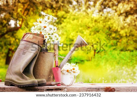 Outdoor gardening tools and flowers/ Spring Gardening tools and a straw hat on btautiful garden background - stock photo