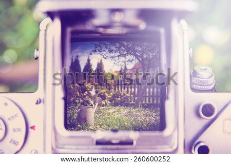 Outdoor gardening tools and flowers through the old camera  with instagram effect retro vintage filter - stock photo