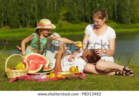 outdoor group portrait of happy family having picnic on green grass in park - stock photo