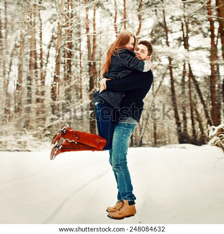 Outdoor happy nice colorful fashion portrait of pretty young beautiful couple posing in winter forest  - stock photo