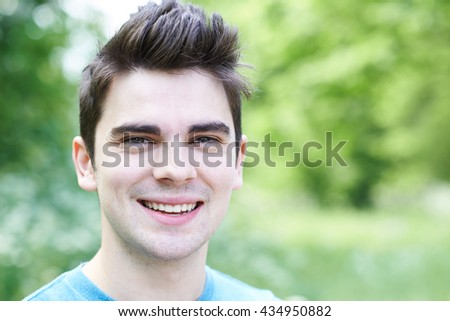 Outdoor Head And Shoulders Portrait Of Smiling Young Man