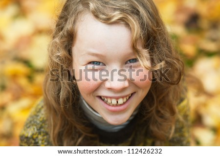 Outdoor high angle portrait of smiling blond girl in autumn park - stock photo