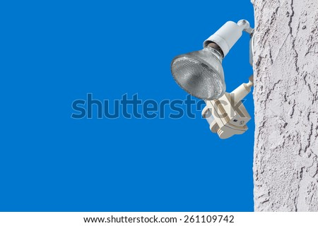 Outdoor home security light and motion sensor on white stucco wall. Residential security adjustable position lamp bulb and detector. Blue sky background. Room for text, copy space.  - stock photo