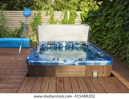 Outdoor hot tub, jacuzzi on the garden. - stock photo