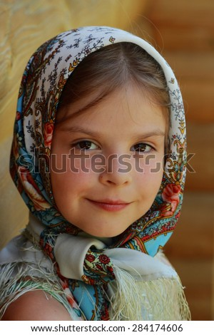 Outdoor image of beautiful smiley little girl wearing Pavloposadsky scarf over wooden background at summer  - stock photo