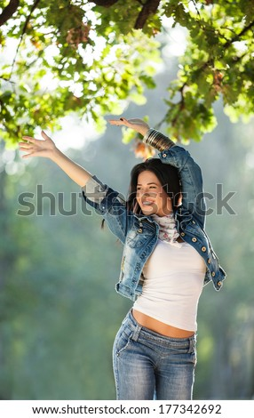 Outdoor image of beautiful young woman smiling, shallow depth of field - stock photo