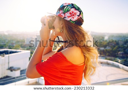 Outdoor lifestyle fashion image of blonde photographer. Young traveller girl taking photo on retro vintage hipster camera. Travel photo, view to the city from the roof. - stock photo