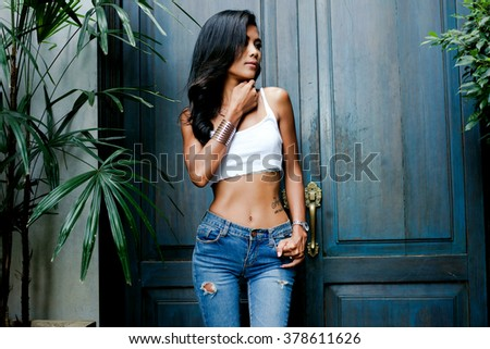Outdoor lifestyle fashion portrait of pretty thai girl,wear casual outfit,attractive beautiful woman with fluffy brunette long hairs,looking away,having fun alone,vacation style,summer look,hairstyle - stock photo