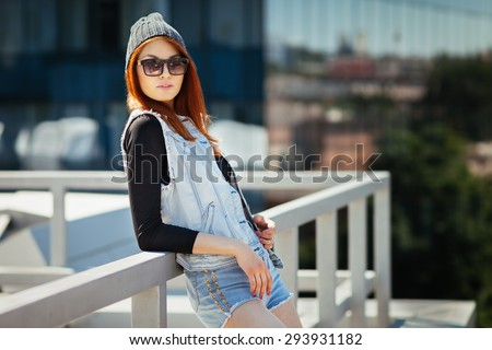 Outdoor lifestyle fashion portrait of pretty young girl, wearing in hipster swag grunge style urban background. Red hair