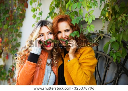 Outdoor lifestyle fashion portrait of two pretty cheerful girls friends, smiling and fooling around. Walking on the autumn city. Wearing stylish bright outerwear with handbags and sunglasses. - stock photo