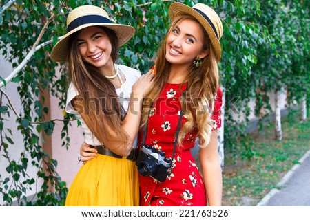 Outdoor lifestyle fashion portraits of two sisters in retro stylish hipster clothes and hats, with retro camera. Two best friends hugs and posing at city park, having fun at nice sunny day. - stock photo