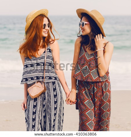 Outdoor lifestyle image of two girls best friends  walking on the sea shore looking at camera laughing, talking. Sisters  strolling along a beach. Stylish summer beachwear abstract print, straw hat.  - stock photo