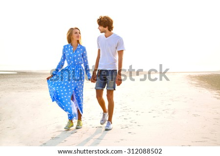 Outdoor lifestyle image of young hipster couple in love, have romantic vacation at the lonely exotic tropical beach, hugs, walking at sunset. - stock photo