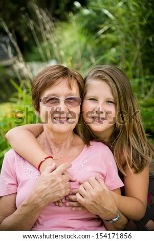 Outdoor lifestyle portrait of grandchild embracing grandmother
