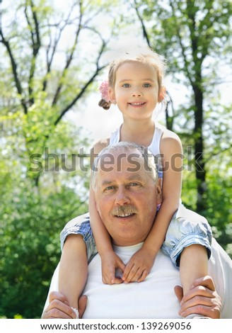 Outdoor lifestyle portrait of granddaughter and grandfather
