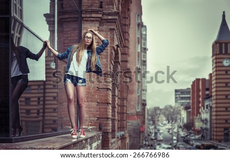 Outdoor lifestyle portrait of pretty young extreme girl, going on the edge of high building parapet, wearing hipster swag dress, urban background. Retro vintage toned image, film simulation. - stock photo