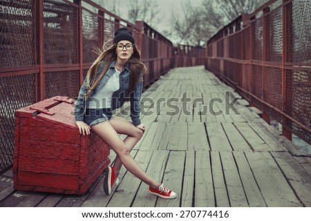 Outdoor lifestyle portrait of pretty young sitting girl, wearing in hipster swag grunge style urban background. Retro vintage toned image, film simulation.