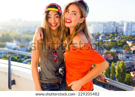 Outdoor lifestyle portrait of two best fiends sisters girls posing on the roof, smiling laughing and having fun, wearing bright outfits swag hats and sunglasses, positive emotions. - stock photo